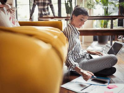Evde bilgisayar başında kalem kağıt ile çalışan kadın