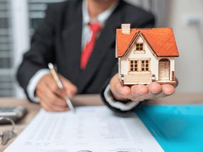 Emlak satış sözleşmesi imzalayan emlakçı ve ev maketi