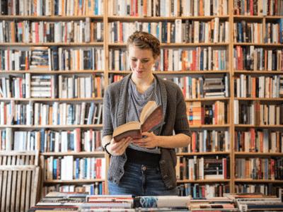Duvar boyunda dolu kitaplık elinde kitap okuyan kadın